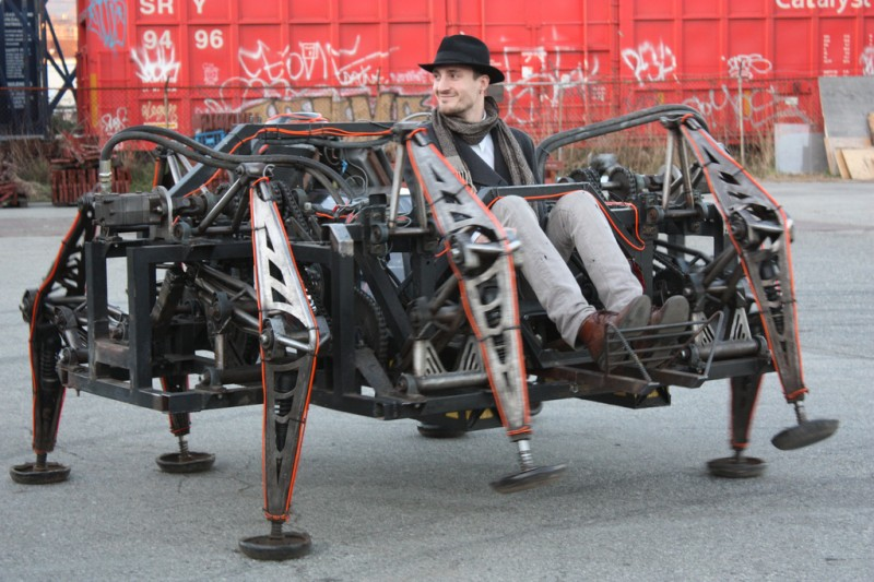Picture of Mr. Christie sitting in a alarge eight-legged robotic walking machine